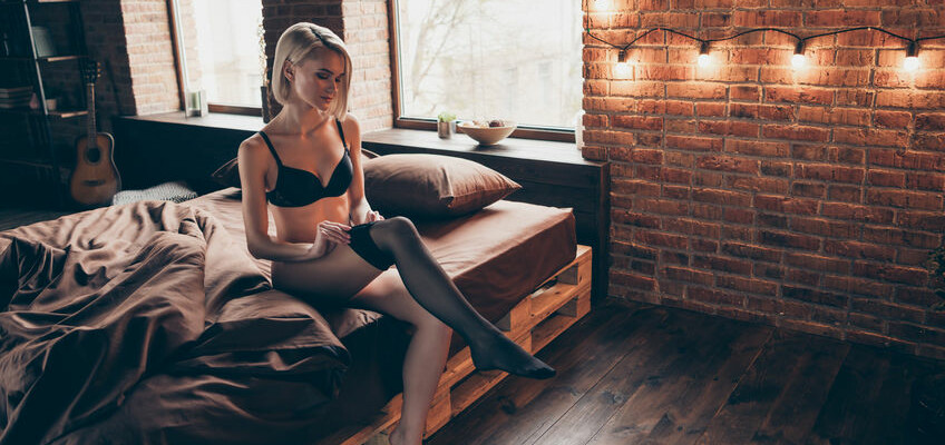 Nice-looking gorgeous attractive winsome luxury elegant slim fit thin feminine lady sitting on bed putting pantyhose off in loft brick industrial style interior room house indoors.